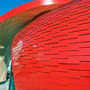 Architects design pavilion with red petal facade. Overlapping shingles are composed of Alucobond Spectra Red tiles featuring a Lumiflon FEVE fluoropolymer resin topcoat. Photo credit: Keith Panel Systems