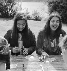 2 girls sitting at picnic table lakeside