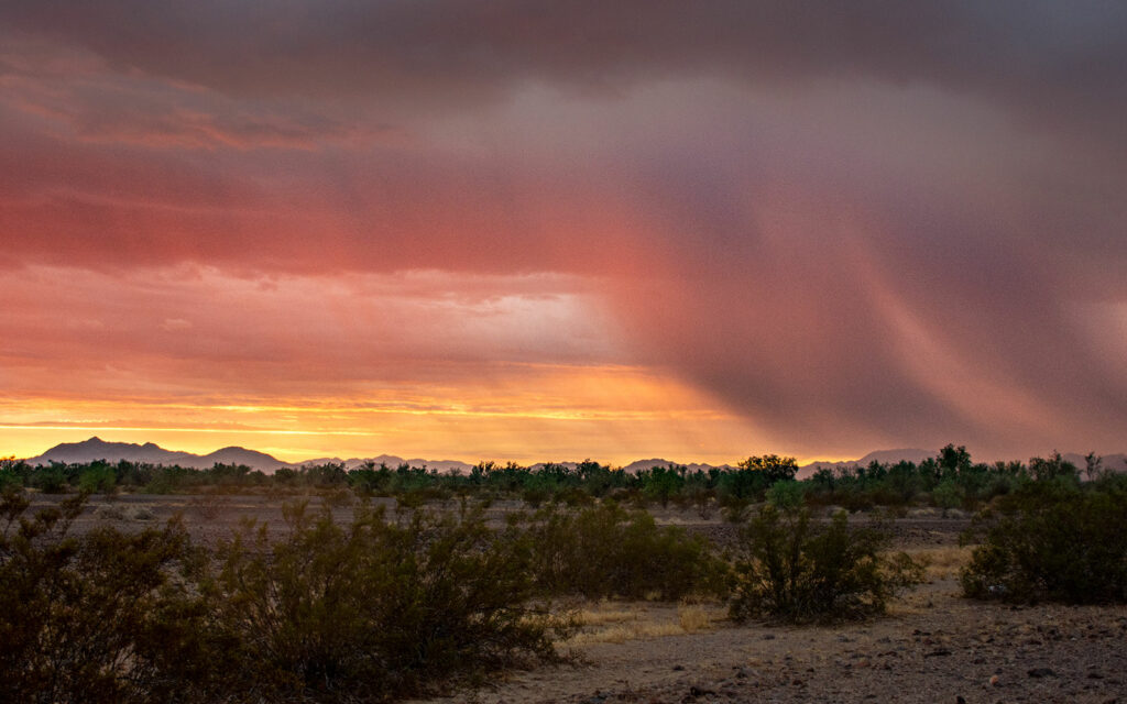 A summer monsoon dumps rain in the distance during a colorful sunset near Blythe, California
