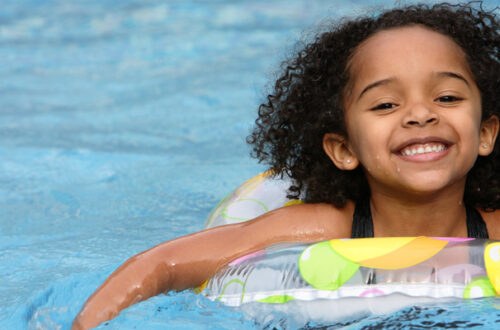 smiling little girl in float tube in pool