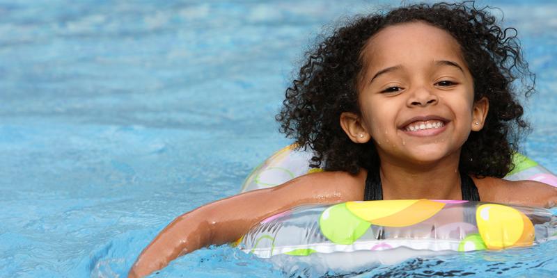 smiling little girl in float tube in pool