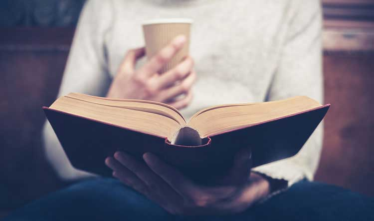 Person reading a book with coffee