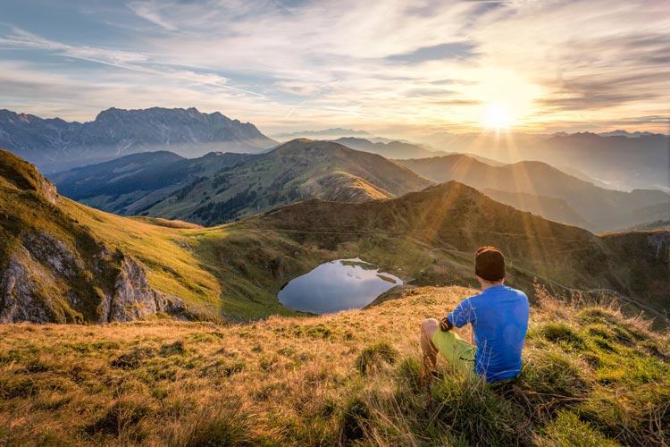 Man sitting on mountain top sun bathing