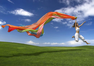 Young beautiful woman jumping with a scarf