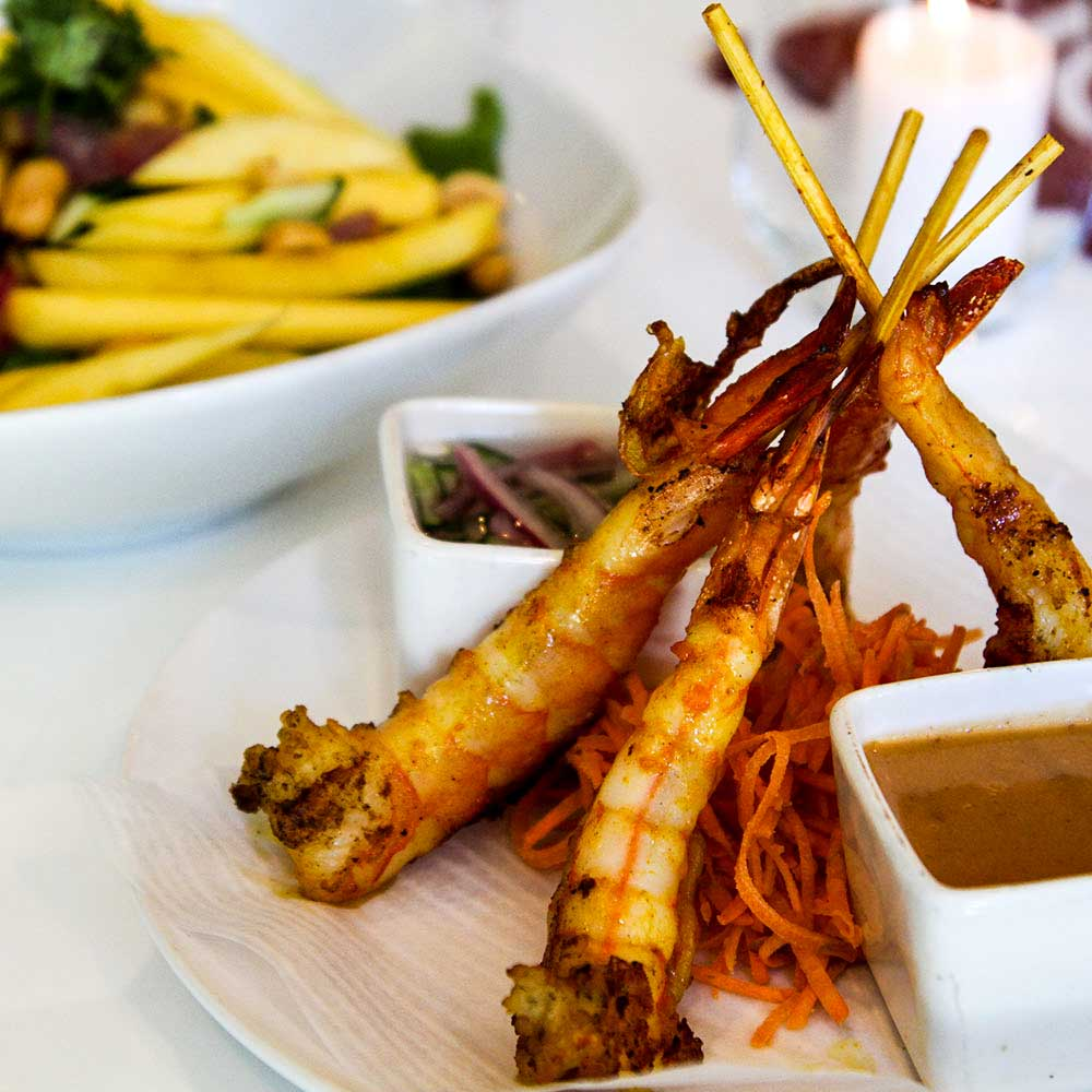 A plate of 3 Fried Tiger Shrimps served with plum sauce and sweet chili dipping sauce