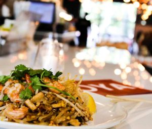 A plate of Pad Thai with shrimp on bar dining table