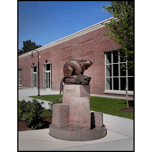photo of bronze sculpture of beaver on log on granite base made of geometric and natural shapes in front of brick building