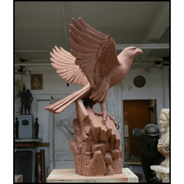 photo of clay model of sculpture of eagle with wings open on rocky surface