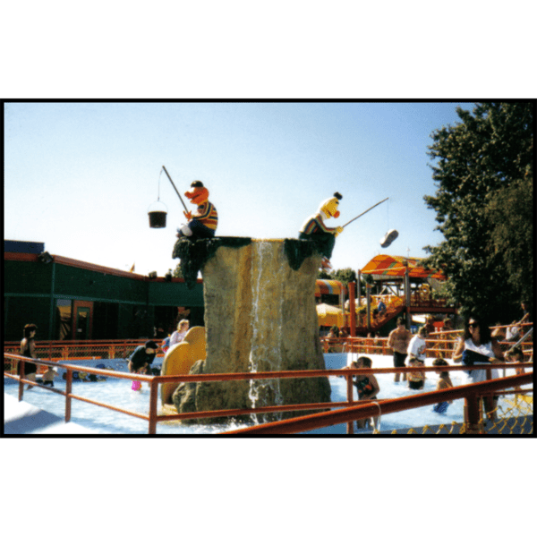 exterior photo of pool with polychromed sculptures of Ernie and Bert fishing at the center