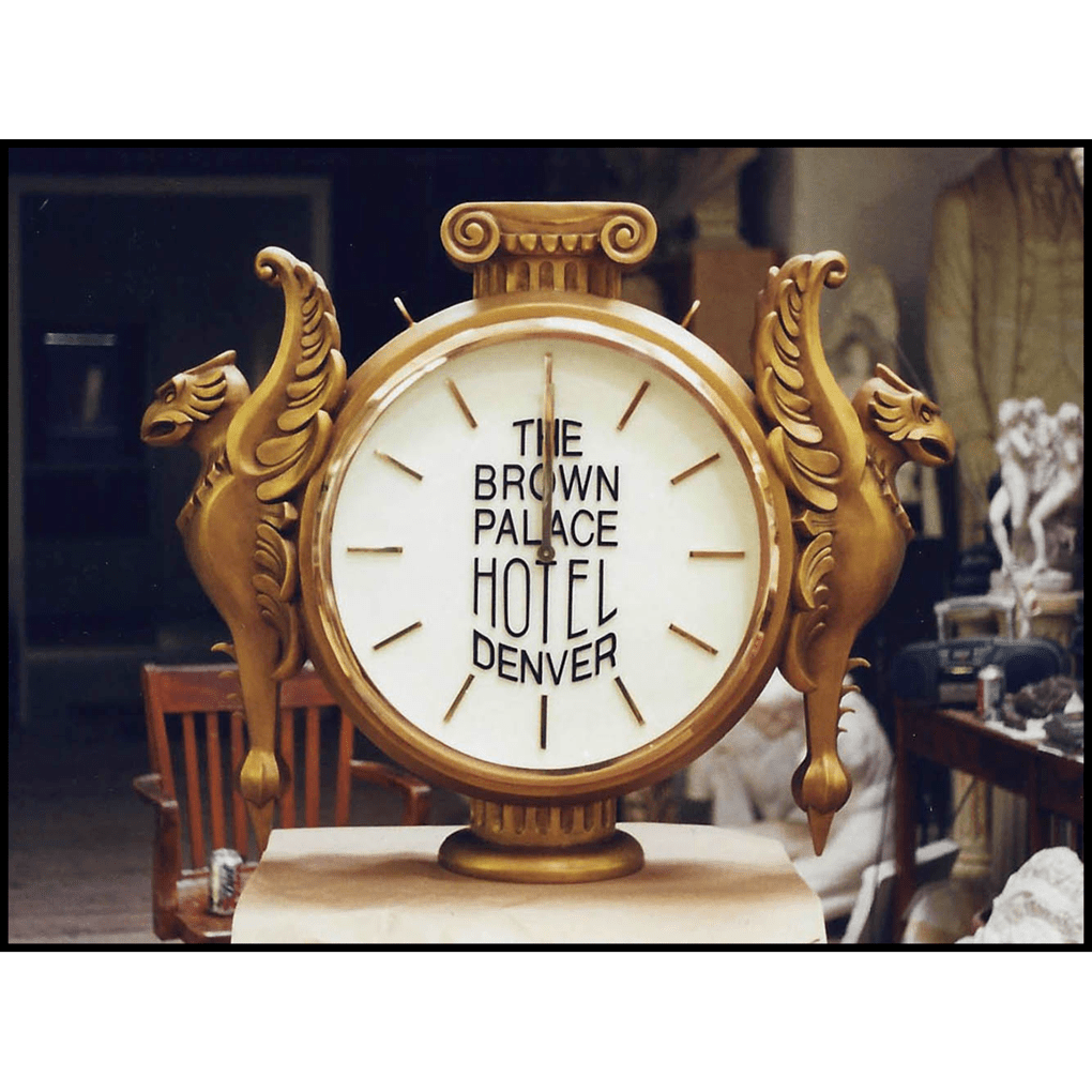 photo of gold clock with white face and griffins in profile on either side
