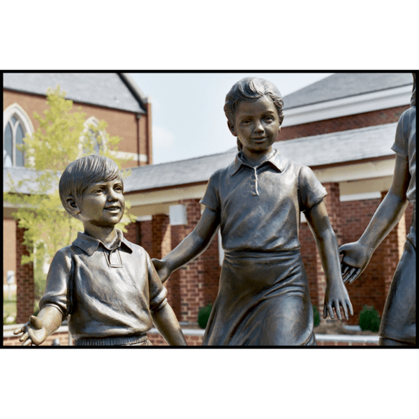 detail photo of bronze sculpture of two children standing in half circle with other children