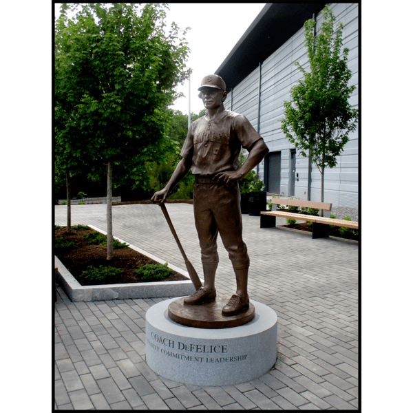 photo of bronze statue of man in baseball uniform holding bat in hand while it rests on ground on a circular granite base in a plaza with building and trees behind