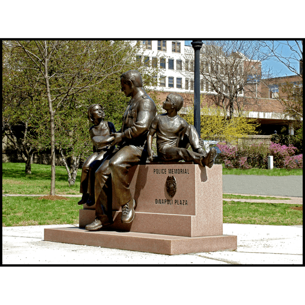 photo of bronze sculpture of adult with two children on stone bench