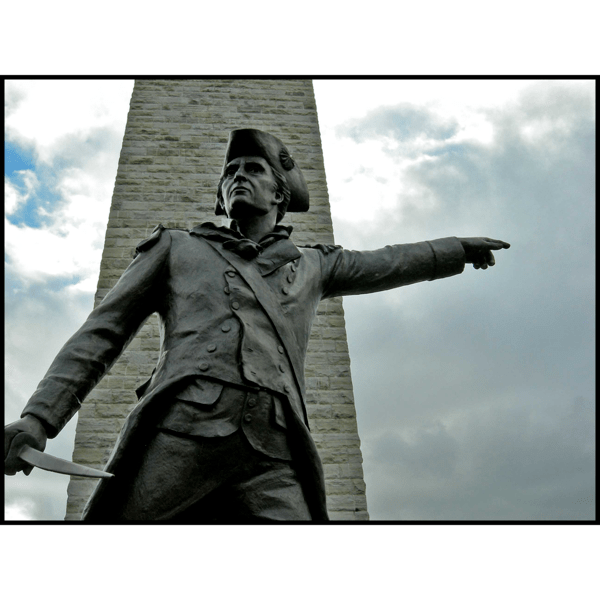 exterior photo of bronze sculpture of John Stark pointing with outstretched arm in front of a obelisk-type monument