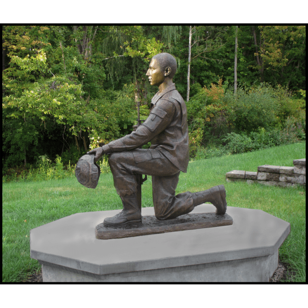 exterior photo of bronze sculpture of Johnny Roberge kneeling and in uniform on concrete base in a park