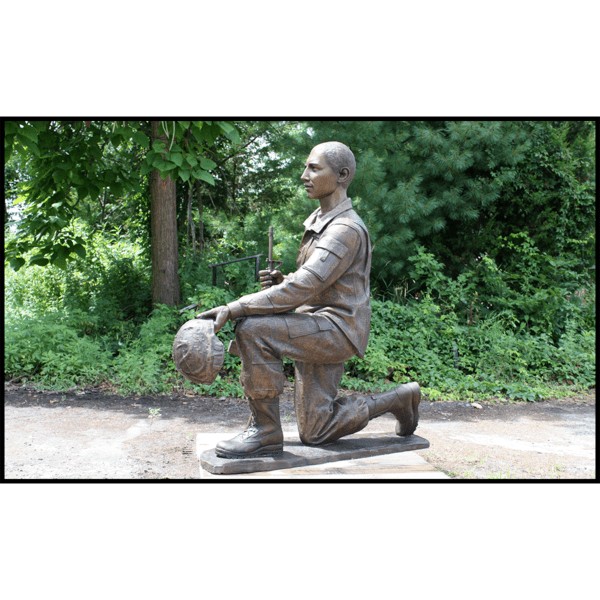 exterior photo of bronze sculpture of Johnny Roberge kneeling and in uniform with green trees behind