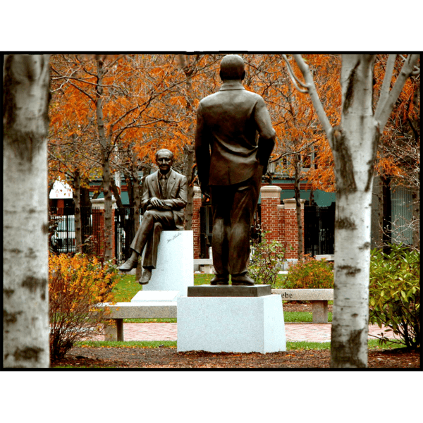 photo of bronze statues of Morris Gaebe and Edward Triangolo on college campus with fall foliage