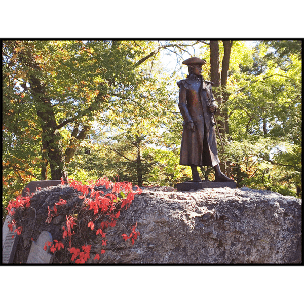 photo of bronze statue of Joseph Warren in uniform holding sword hilt at his side atop a large puddingstone with red leaves on left side