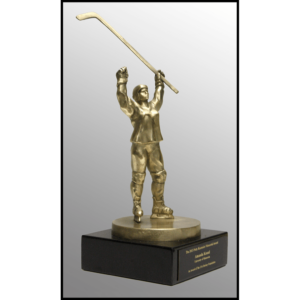 photo of gold-colored sculpture of female hockey player in gear raising her stick in the air and other arm raised atop a black stone base with plaque