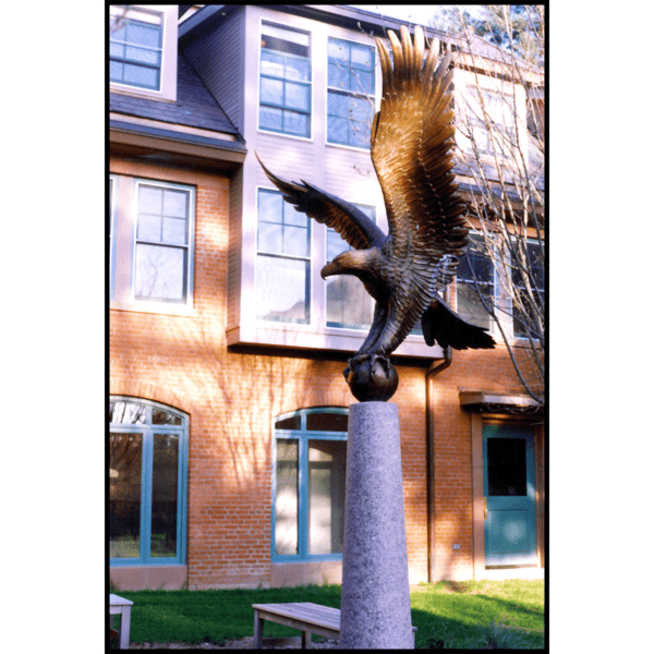 photo of bronze sculpture of eagle perched on ball with open wings atop tall pedestal in front of a brick building