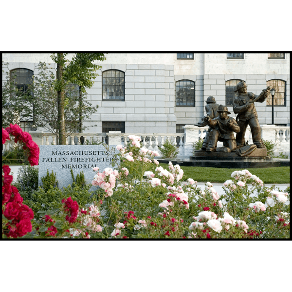 photo of bronze sculpture of three firefighters in action stances on a stone base in front of white stone building with grass and flowers in foreground