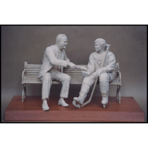photo of white-colored sculpture of George Matthews on bench with a female in hockey gear atop a wood base