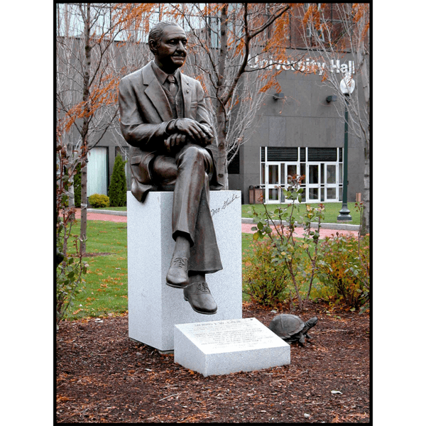 photo of bronze statue of Morris Gaebe sitting on stone base on college campus