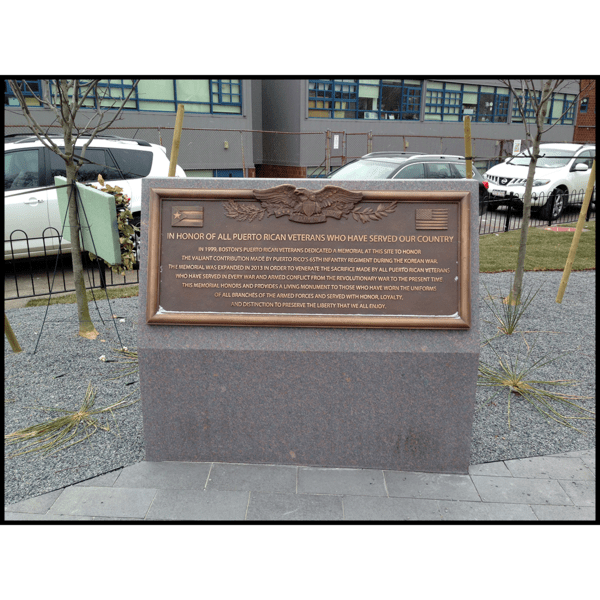 photo of bronze plaque with text and eagle in relief at the top on a granite base