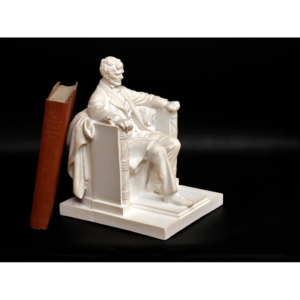 photo of white-colored Lincoln Memorial reduction sculpture with a red book leaning on it
