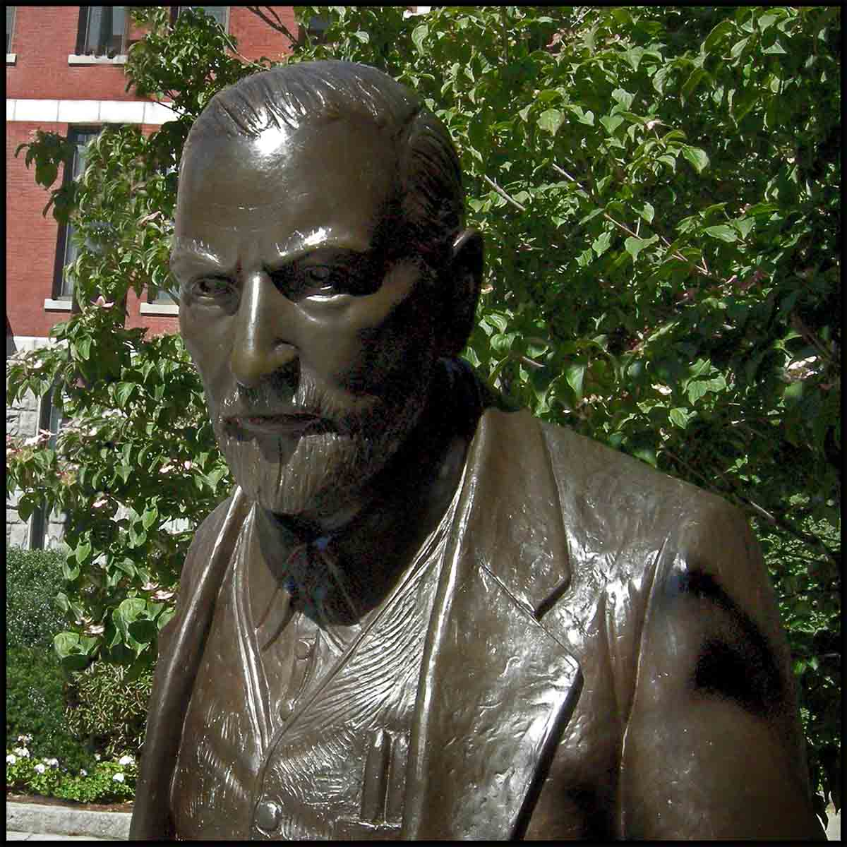 photo closeup of face of bronze sculpture of Sigmund Freud sitting on a stone bench in a plaza with trees behind