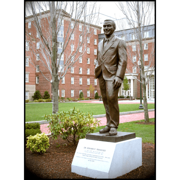photo of bronze statue of Edward Triangolo standing on stone base on college campus