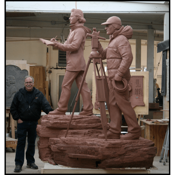 photo of clay model of sculpture of man and woman in winter gear with theodolite on tripod and woman taking notes, standing on rock surface with artist Robert Shure in his studio