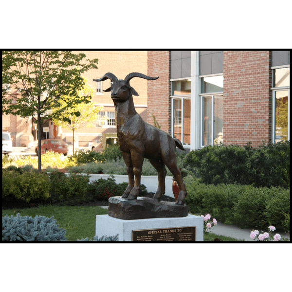 photo of bronze sculpture of goat standing on sculpted incline