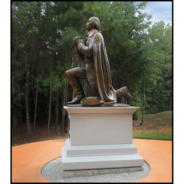 exterior photo of bronze sculpture of George Washington kneeling and praying on stone base