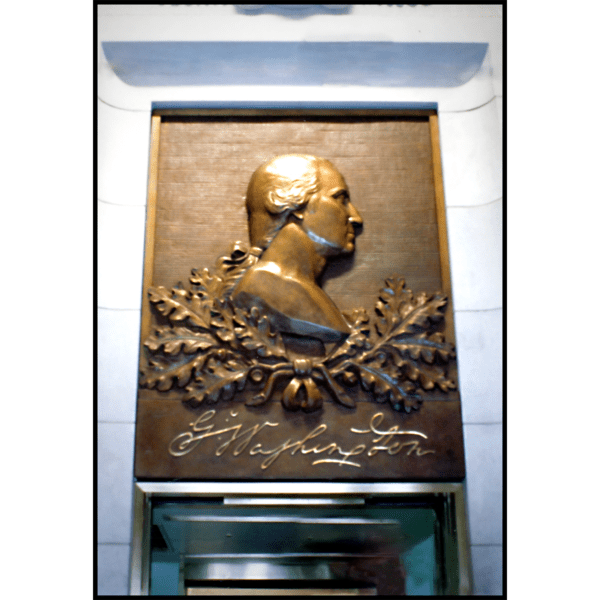 photo of bronze relief portrait of George Washington in profile with oak leaves and his signature above a doorway