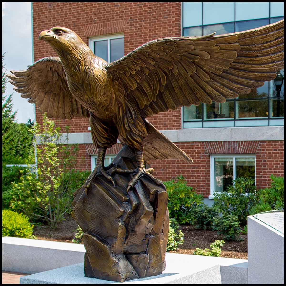 photo of bronze sculpture of eagle with wings open on rocky surface on top of granite base surrounded by other stonework in brick plaza in front of a brick building