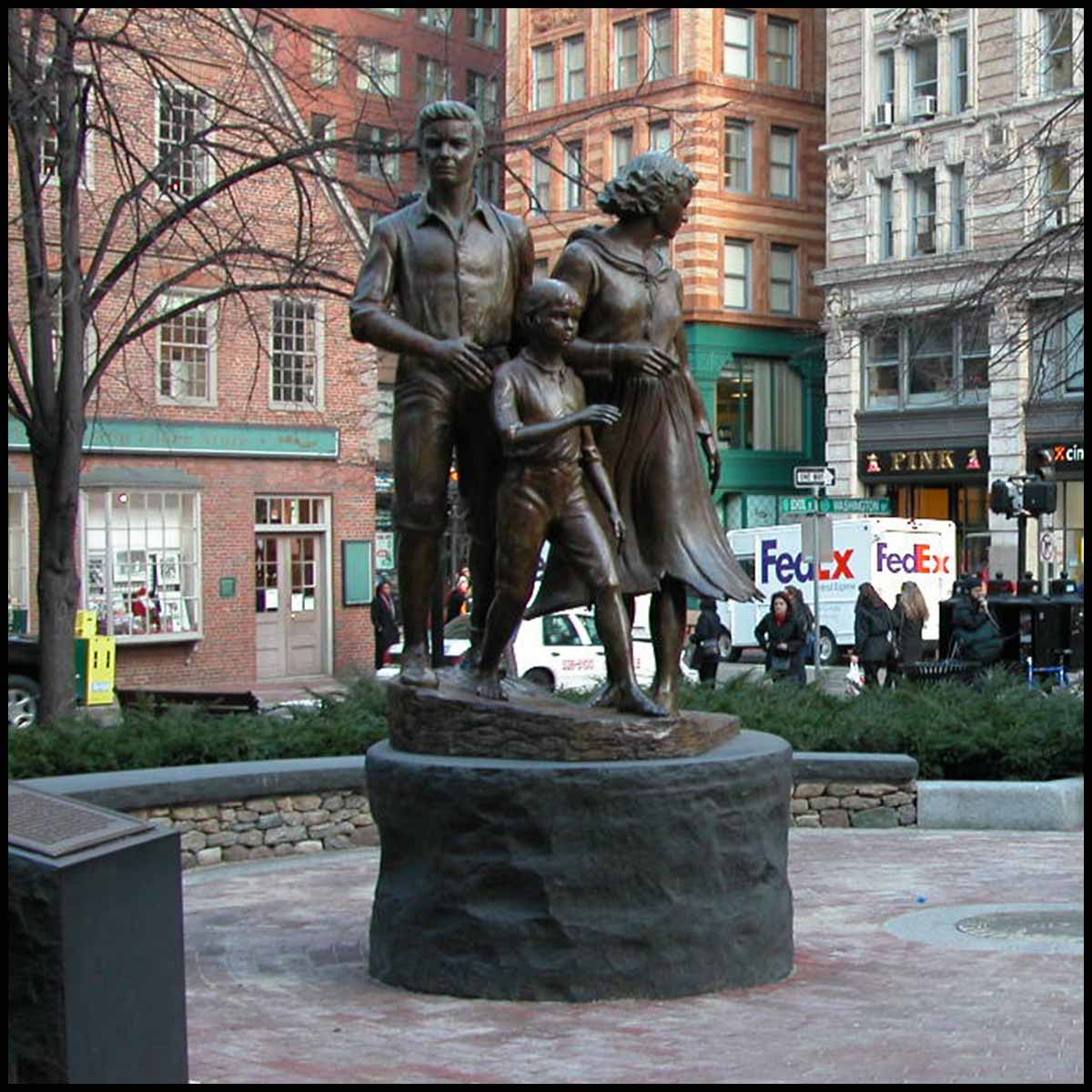 photo of bronze-colored sculpture of male, female, and child in movement on round stone base in hardscaped plaza with buildings and streets surrounding it