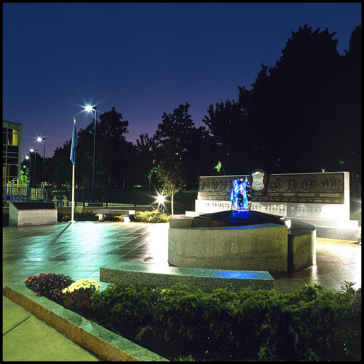 exterior photo of plaza lit at night with large granite memorials