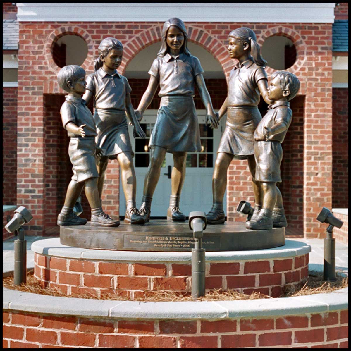 photo of bronze sculpture of five children standing in half circle holding hands atop brick-faced pedestal