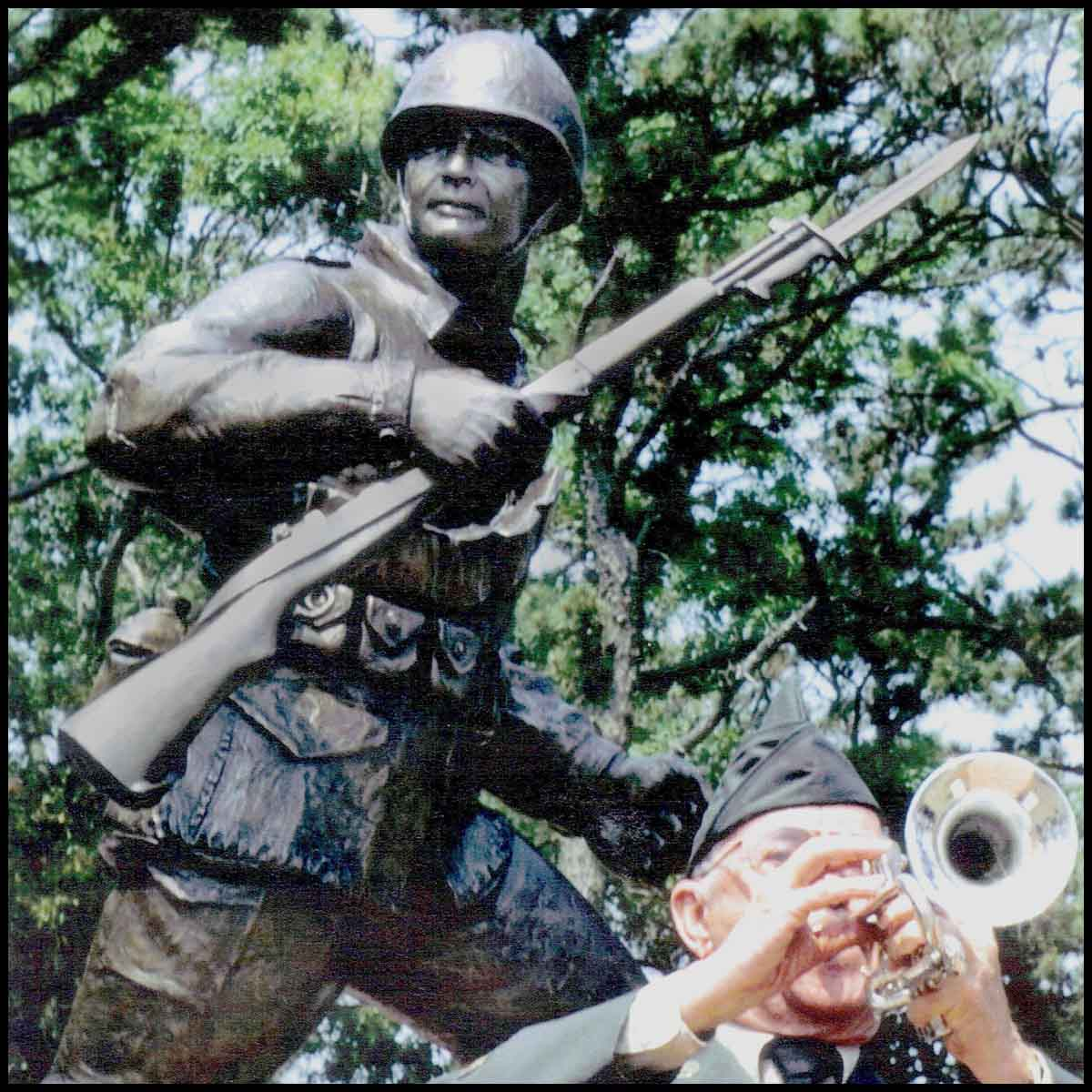 closeup photo of bronze-colored sculpture of soldier holding rifle in action on incline with trees behind and veteran in dress uniform in front playing trumpet