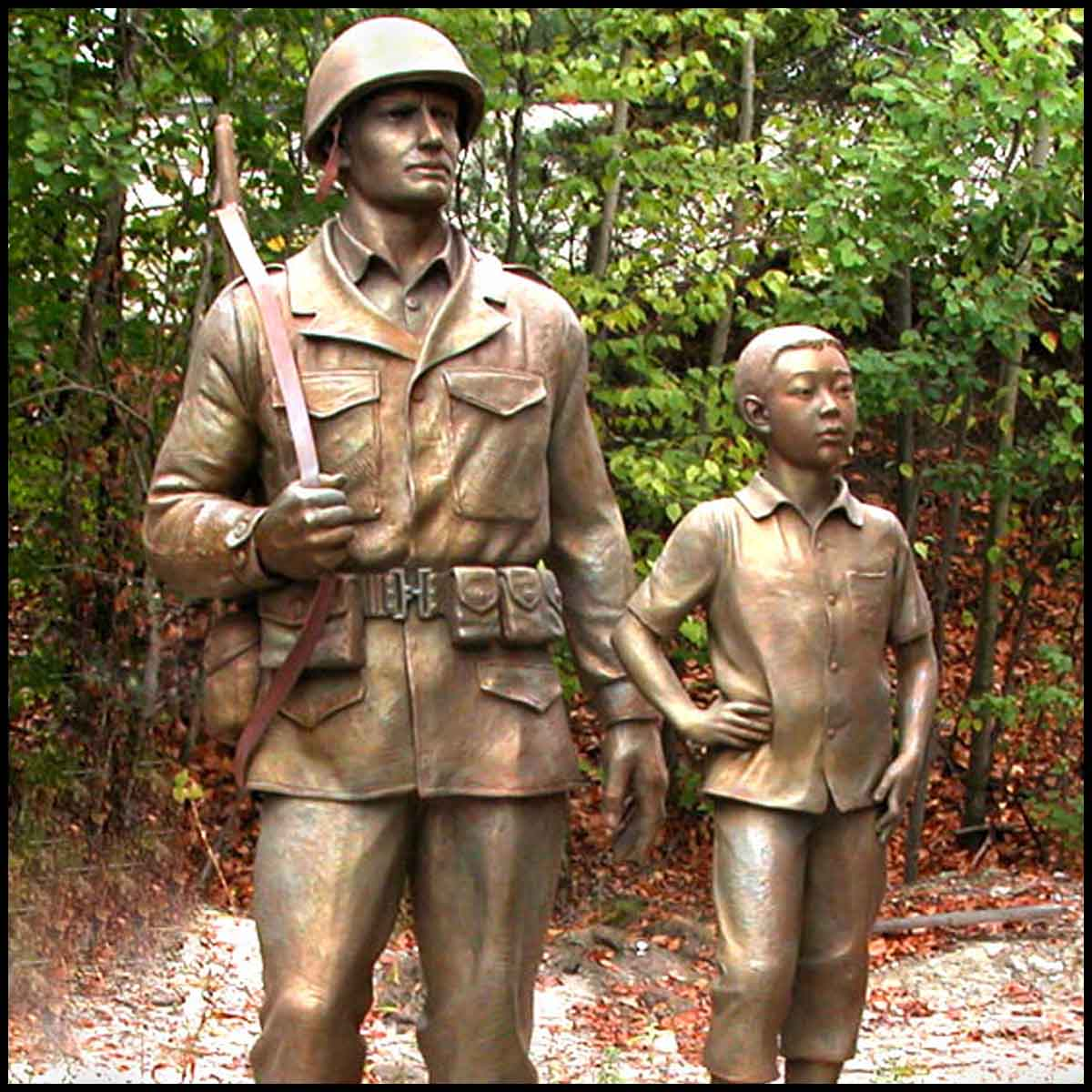 photo of bronze-colored sculpture of American male soldier and Korean boy with trees behind