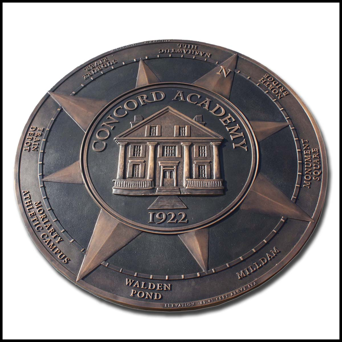 photo of bronze floor medallion with relief sculpture of building and compass elements