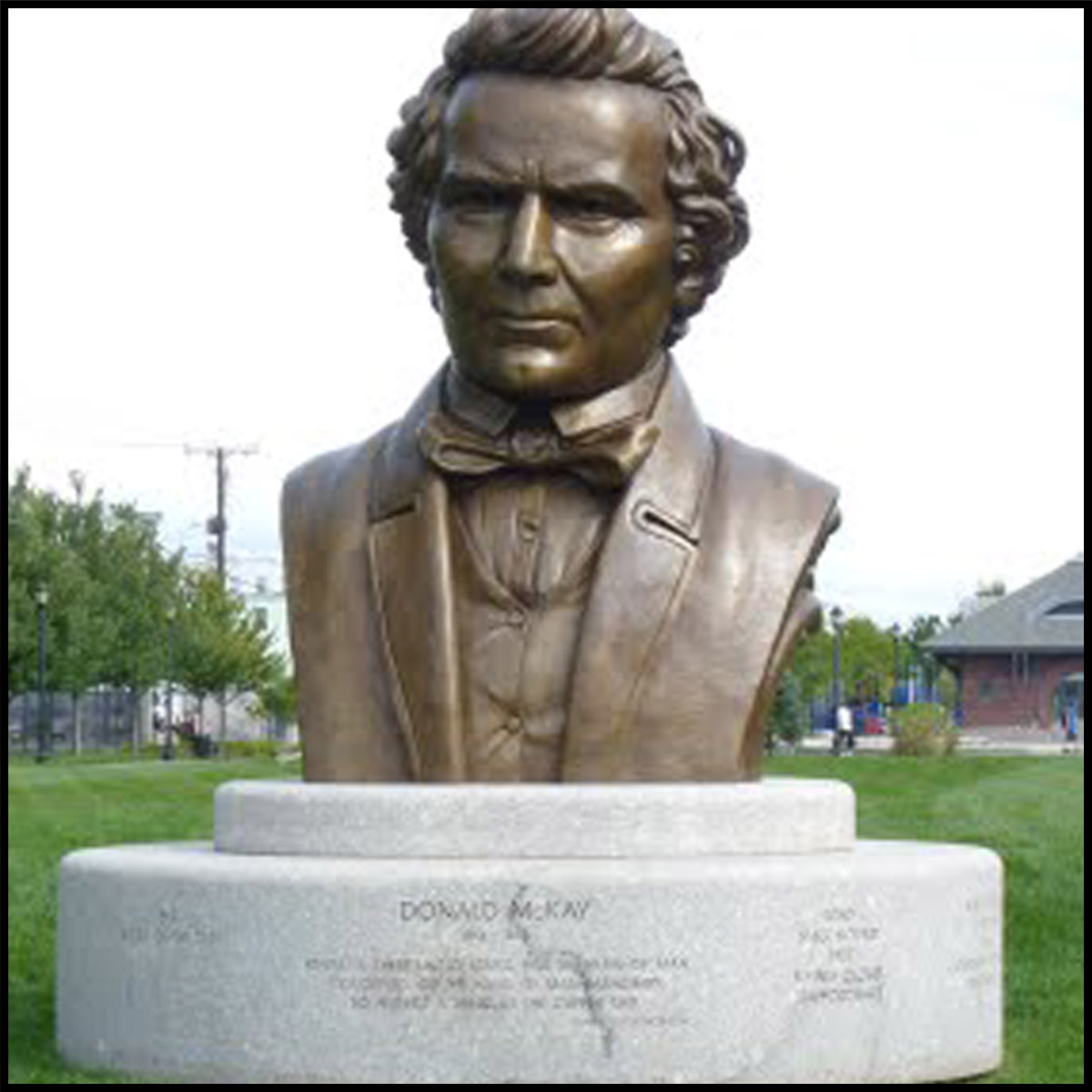 photo of monumental bronze bust of Donald McKay on stone base outdoors on grass