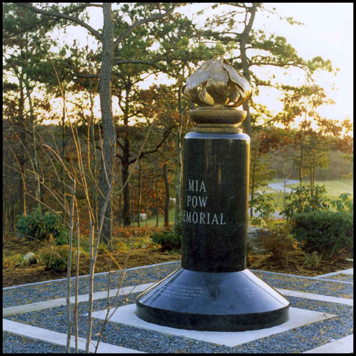 photo of bronze sculpture of flame on black granite base with inscriptions in hardscaped area with surrounding trees and greenery