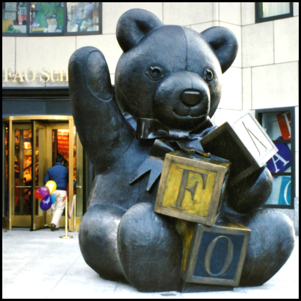 photo of bronze teddy bear with arm raised and holding blocks in front of city store