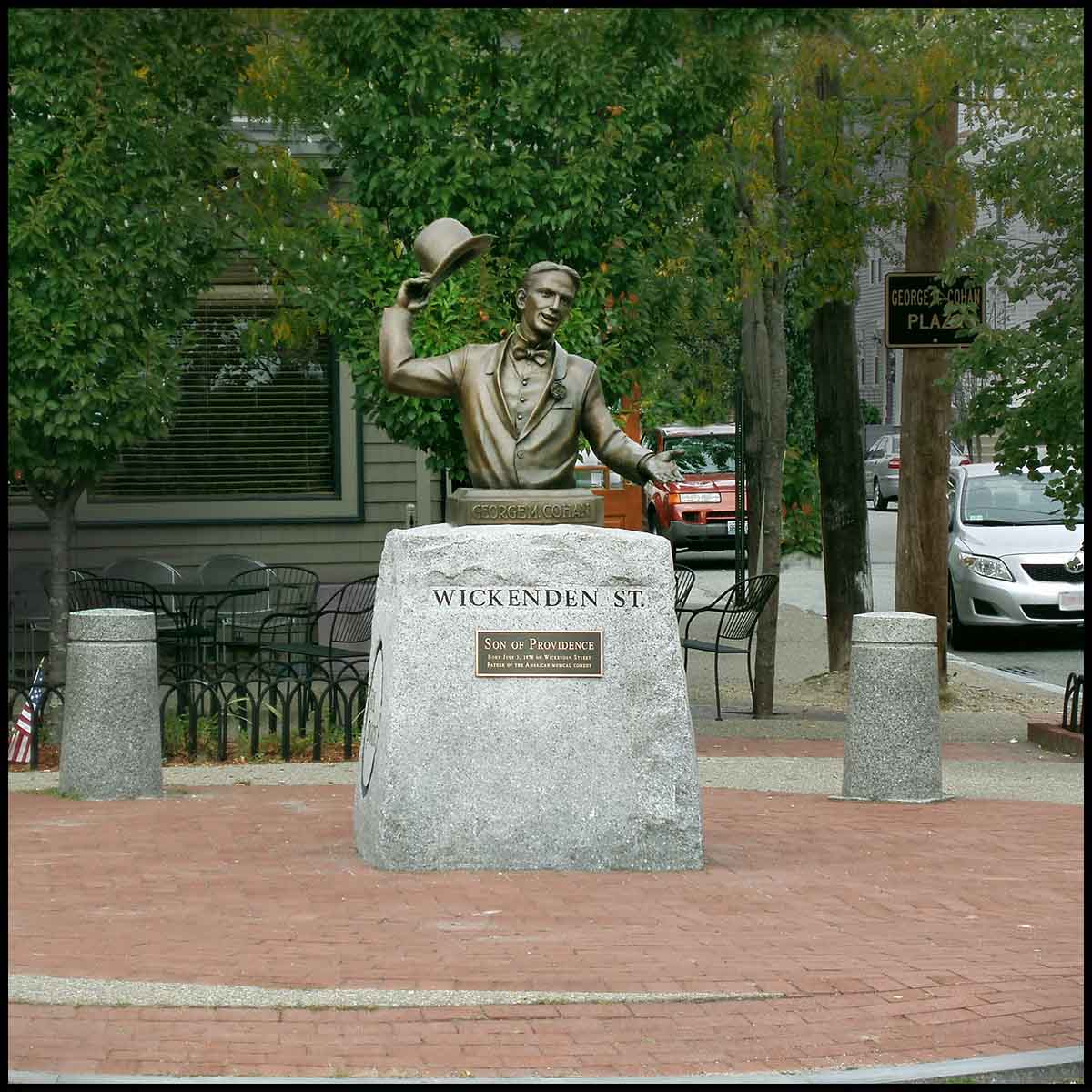 exterior photo of bronze sculpture of George Cohan's upper torso and arms on a stone base on brick plaza