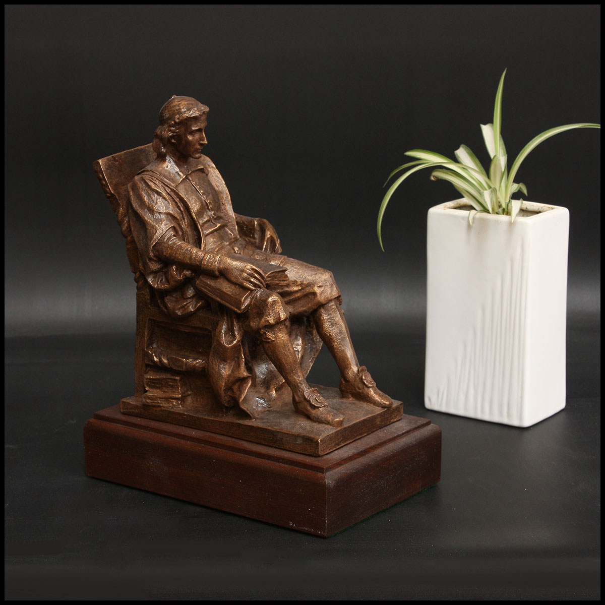 photo of bronze-colored sculpture of John Harvard seated in a chair atop a wood base beside a white vase with a plant