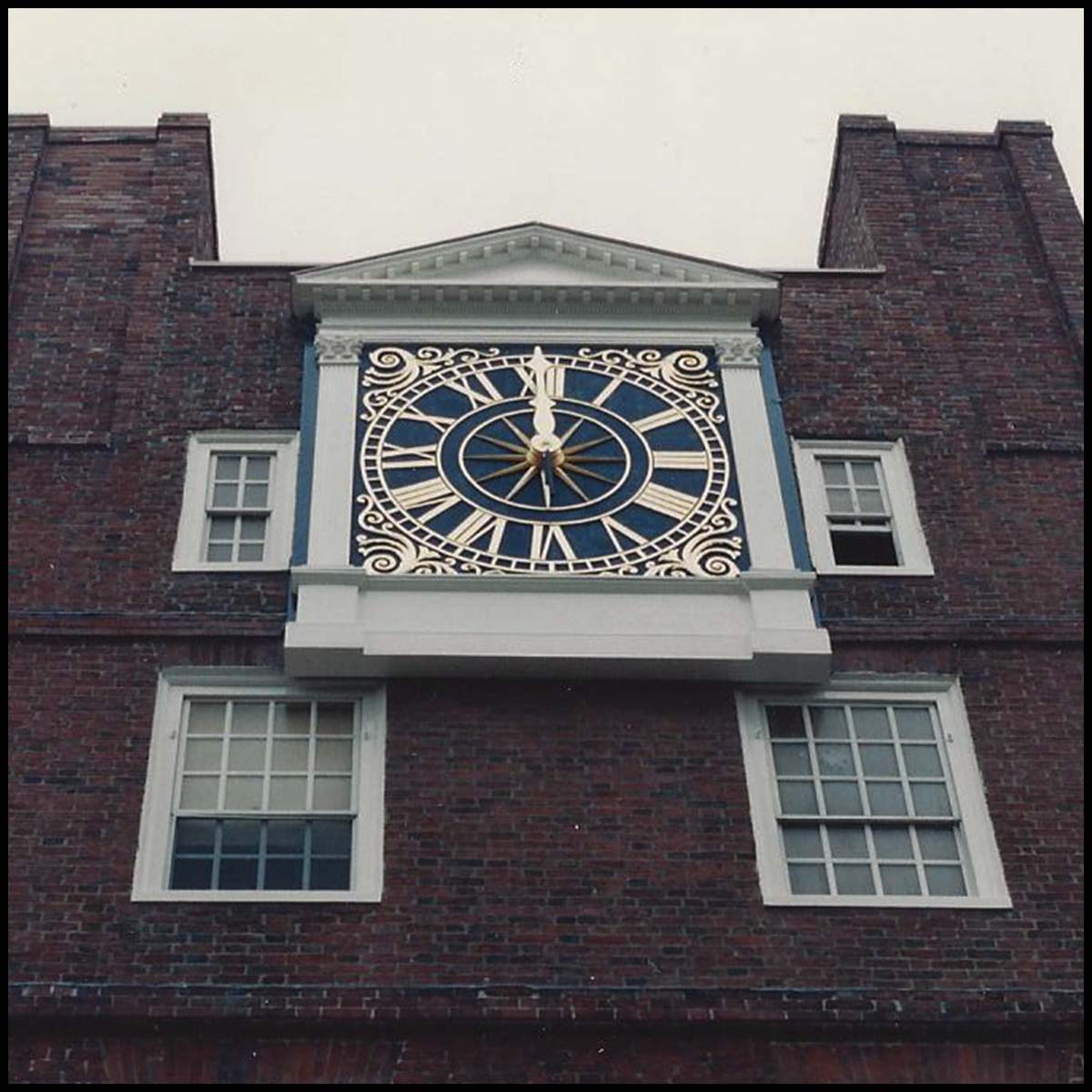 photo of blue and gold clock topped with pediment on a brick building