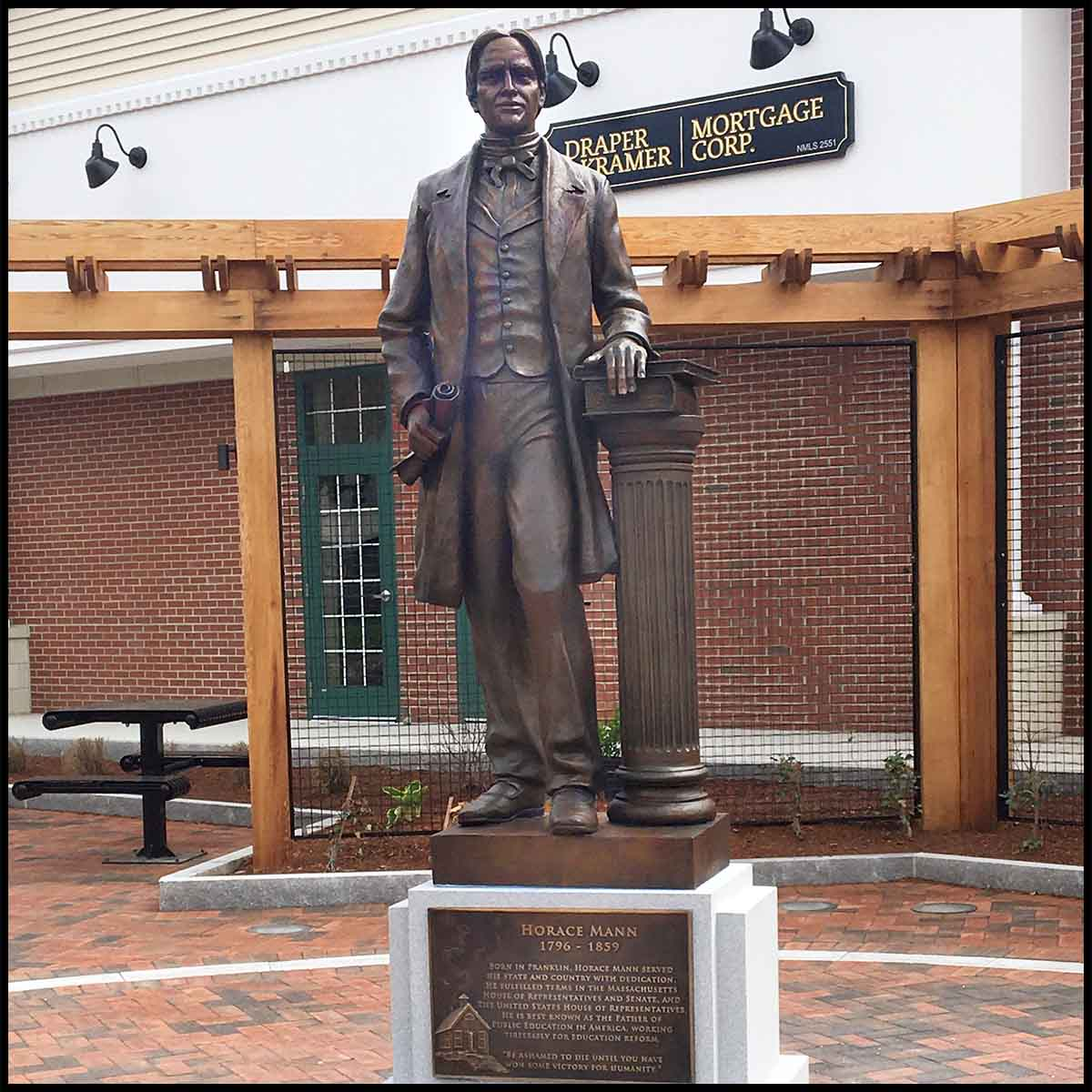 photo of bronze-colored statue of Horace Mann holding scroll and standing beside column with books, atop granite pedestal with bronze-colored plaque in a hardscaped plaza with building behind