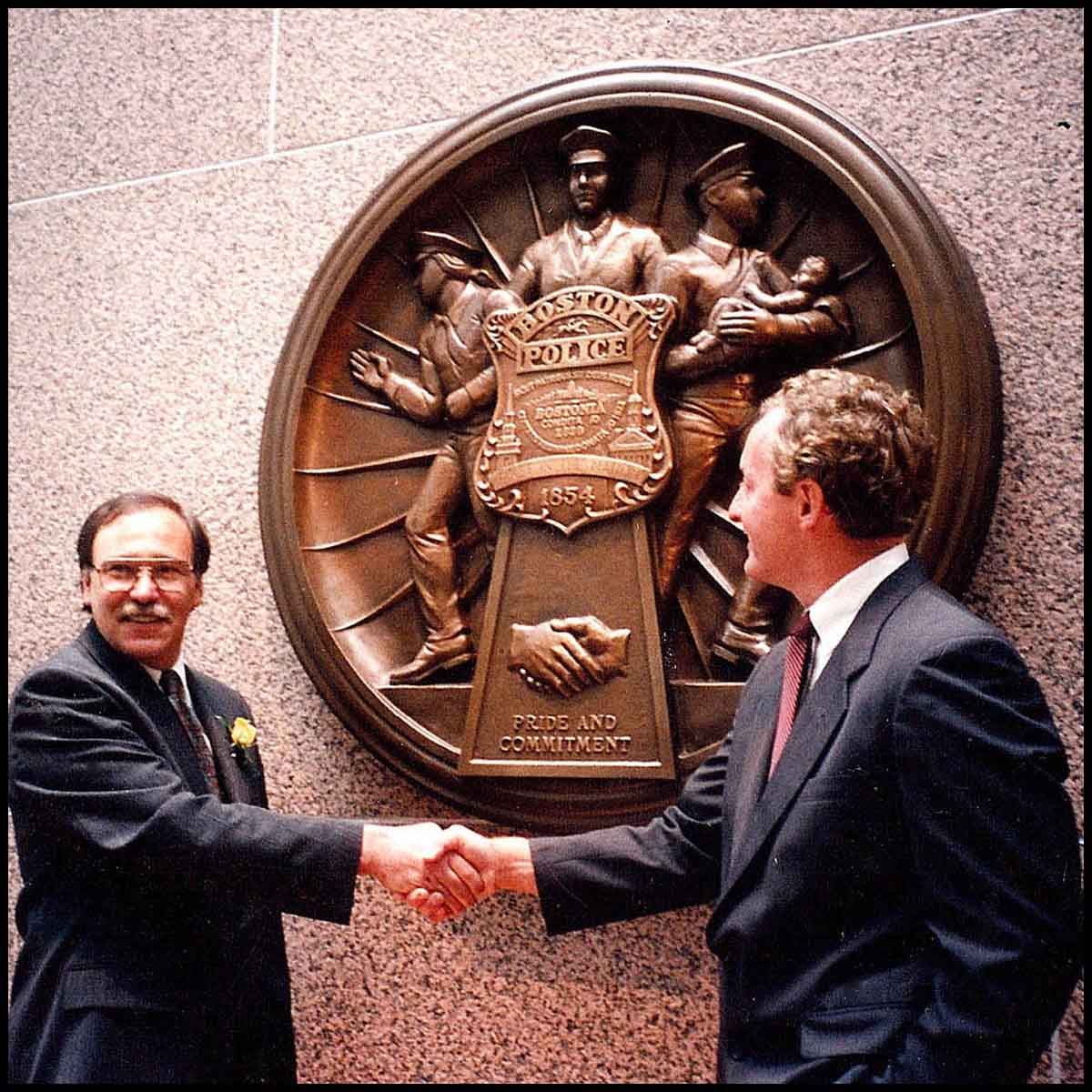 photo of sculptor Robert Shure shaking hands with Boston official at dedication ceremony for Police and Fire department plaques, standing in front of large, bronze-colored police plaque mounted on stone wall